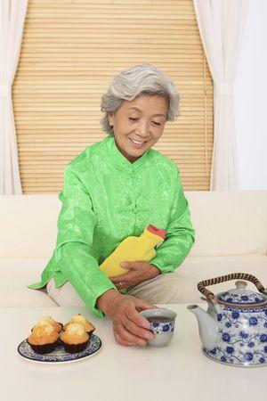 w�rmflasche: Senior Frau mit W�rmflasche zu erreichen, die chinesischen Tee