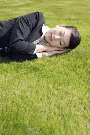 Businesswoman sleeping on grass photo
