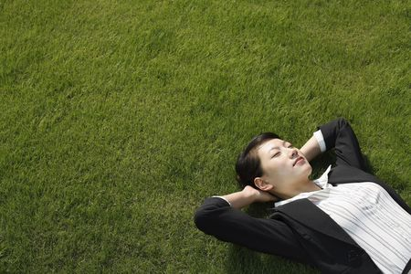 Businesswoman lying down on grass