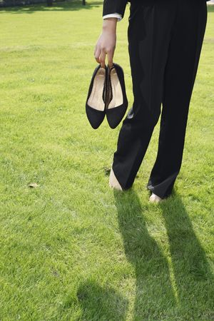 Businesswoman holding heels while walking barefoot on grass
