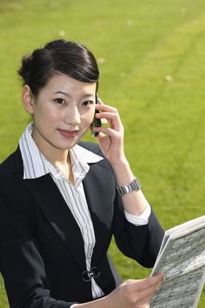 Businesswoman reading newspaper while talking on the phone photo