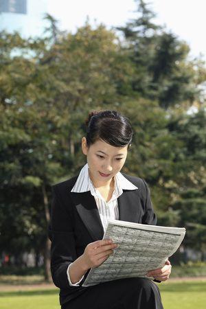 Businesswoman reading newspaper photo