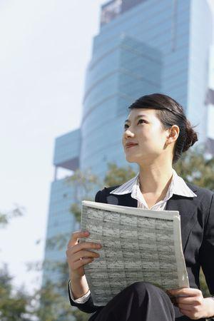 reading newspaper: Businesswoman reading newspaper Stock Photo