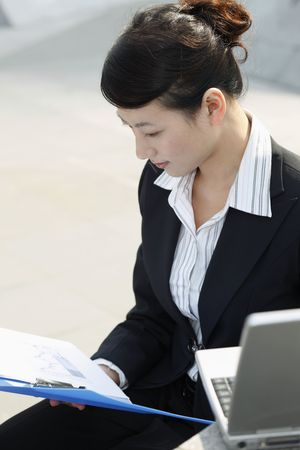 Businesswoman reading documents in file photo