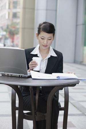 Businesswoman reading documents in file while holding coffee photo