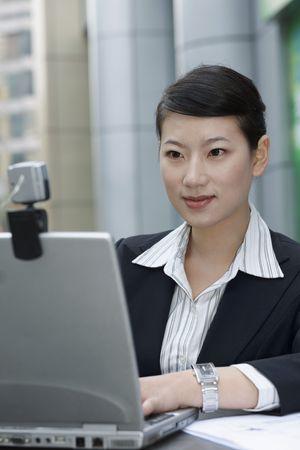 Businesswoman having meeting through webcam photo