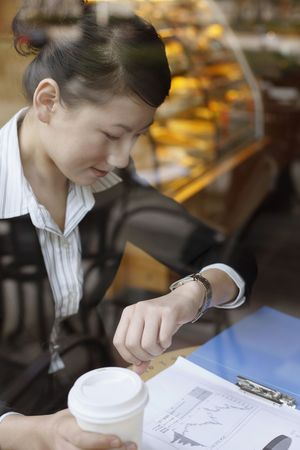 Businesswoman looking at her watch, checking time photo