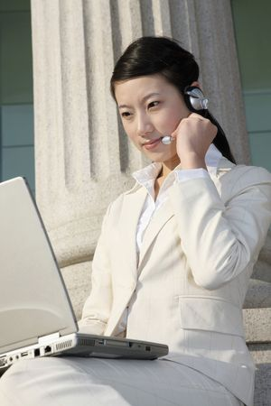 Businesswoman using headset and laptop photo