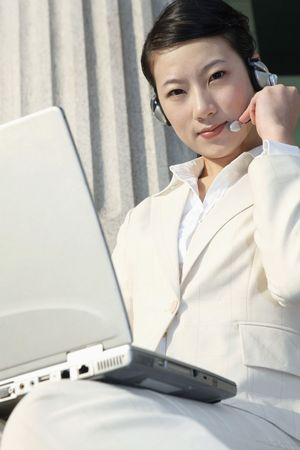 Businesswoman using headset and laptop Stock Photo - 4636024