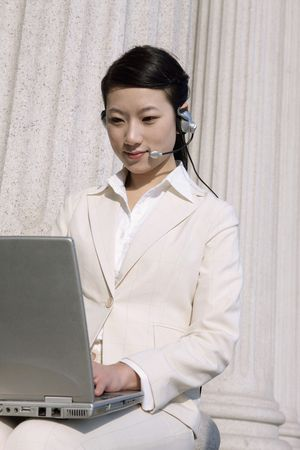 Businesswoman using headset and laptop Stock Photo - 4636399