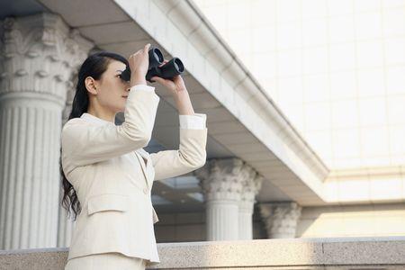Businesswoman looking through binoculars Stock Photo - 4636096