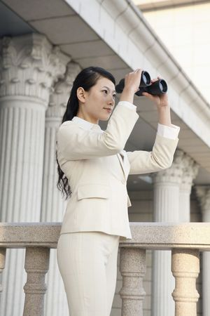 Businesswoman looking through binoculars Stock Photo - 4636049