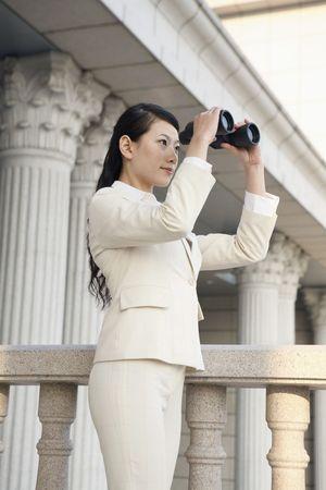 Businesswoman looking through binoculars Stock Photo - 4636049