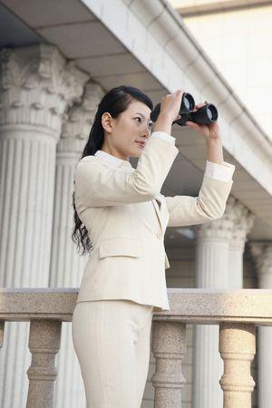Businesswoman looking through binoculars Stock Photo - 4636119