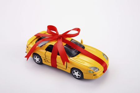 toy car: Yellow toy car gift wrapped with red ribbon Stock Photo