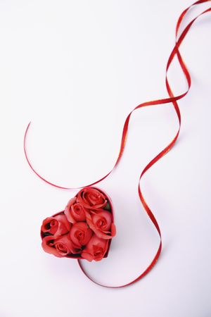 Red heart-shaped box with roses, ribbon at its side