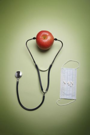 Stethoscope with an apple, surgical mask and pills at the side photo