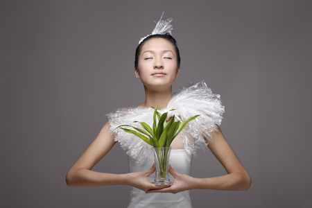 tube top: Woman wearing plastic accessories holding plant in a vase Stock Photo