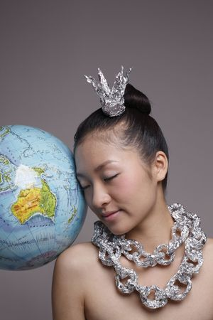 Woman wearing foil accessories leaning against globe photo