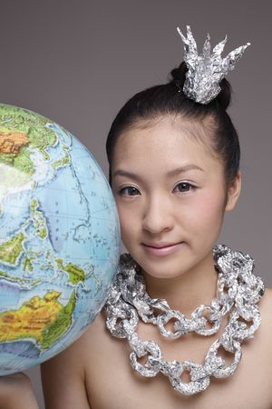 Woman wearing foil accessories holding globe Stock Photo - 4653983