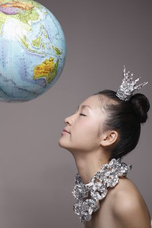 Woman wearing foil accessories with globe above at the top photo