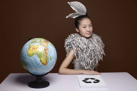 Woman wearing newspaper accessory and shredded newspaper collar photo