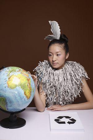 Woman wearing newspaper accessory and shredded newspaper collar looking at globe photo