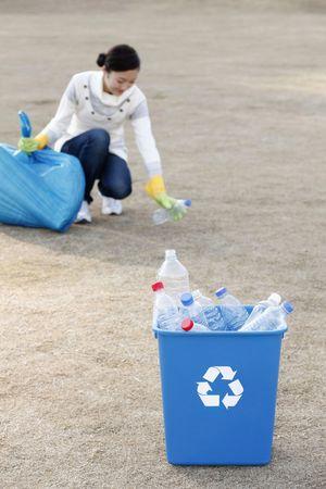 kunststof fles: Vrouw die plastic zak en het oppakken van plastic fles Stockfoto