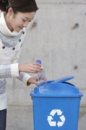 kunststof fles: Vrouw brengen plastic fles in de recycling bin