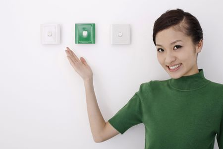 switches: Woman showing light switches at her side