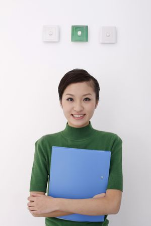 Woman holding file standing under light switches Stock Photo