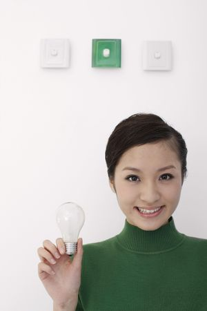 Woman standing under light switches holding lightbulb Stock Photo