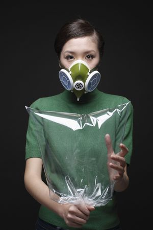 Woman wearing gas mask holding clear plastic bag photo