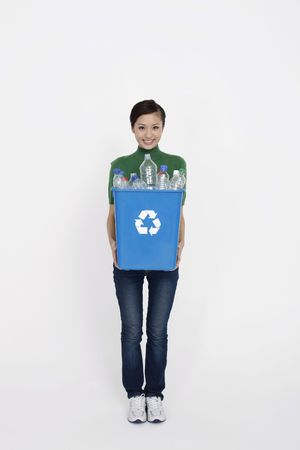 Woman holding recycling bin with plastic bottles in it