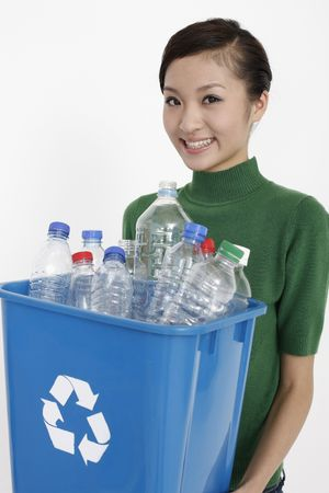 Woman holding recycling bin with plastic bottles in it photo
