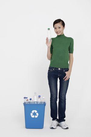kunststof fles: Vrouw bedrijf plastic fles met recycling bin op de grond Stockfoto