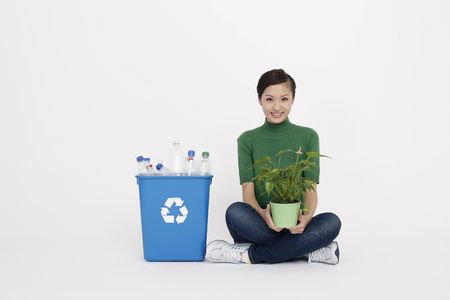 crossing legs: Woman holding potted plant sitting next to recycling bin Stock Photo
