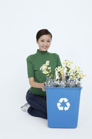Woman holding recycling bin with flowers in plastic bottles Stock Photo - 4653820