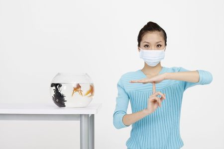 Woman wearing surgical mask showing timeout gesture photo
