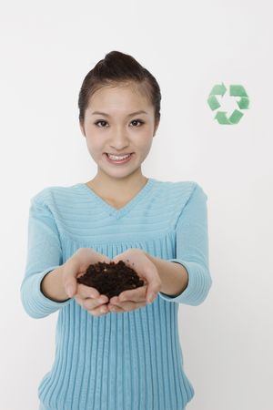 Woman showing soil in her palms, recycling sign the background Stock Photo