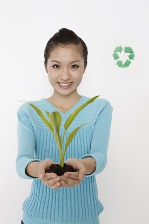 Woman showing plant in her palms, recycling sign the background