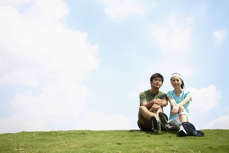 Man and woman sitting on the field Stock Photo