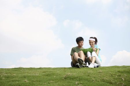 Man and woman reading book together on the field Stock Photo
