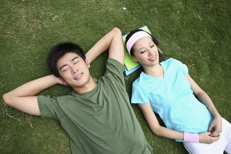 Man and woman relaxing on the field, eyes closed