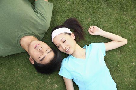 Man en vrouw liggen op het veld, ogen dicht Stockfoto