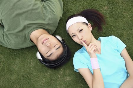 eyes closing: Man listening to music on the headphones, woman with finger on lips Stock Photo