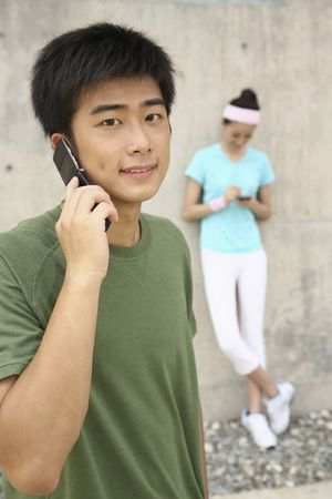 Man talking on the phone, woman text messaging on the phone Stock Photo