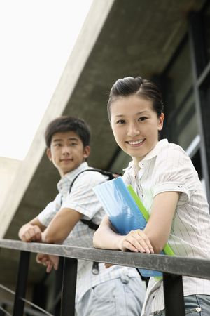 Man and woman standing on the stairs, smiling at the camera photo