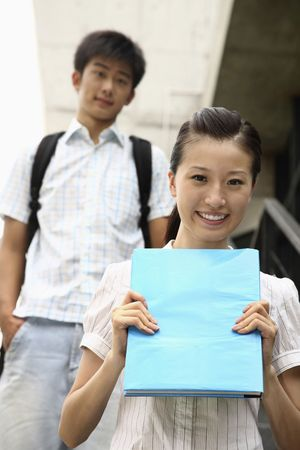 Woman smiling and holding book, man standing in the background photo