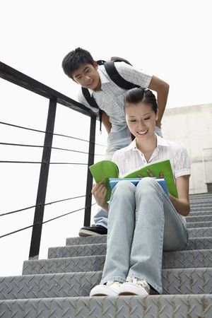 Woman sitting on the stairs reading book, man peeking from behind photo
